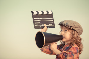 Kid holding clapper board and shouting through vintage megaphone. Cinema concept. Retro style