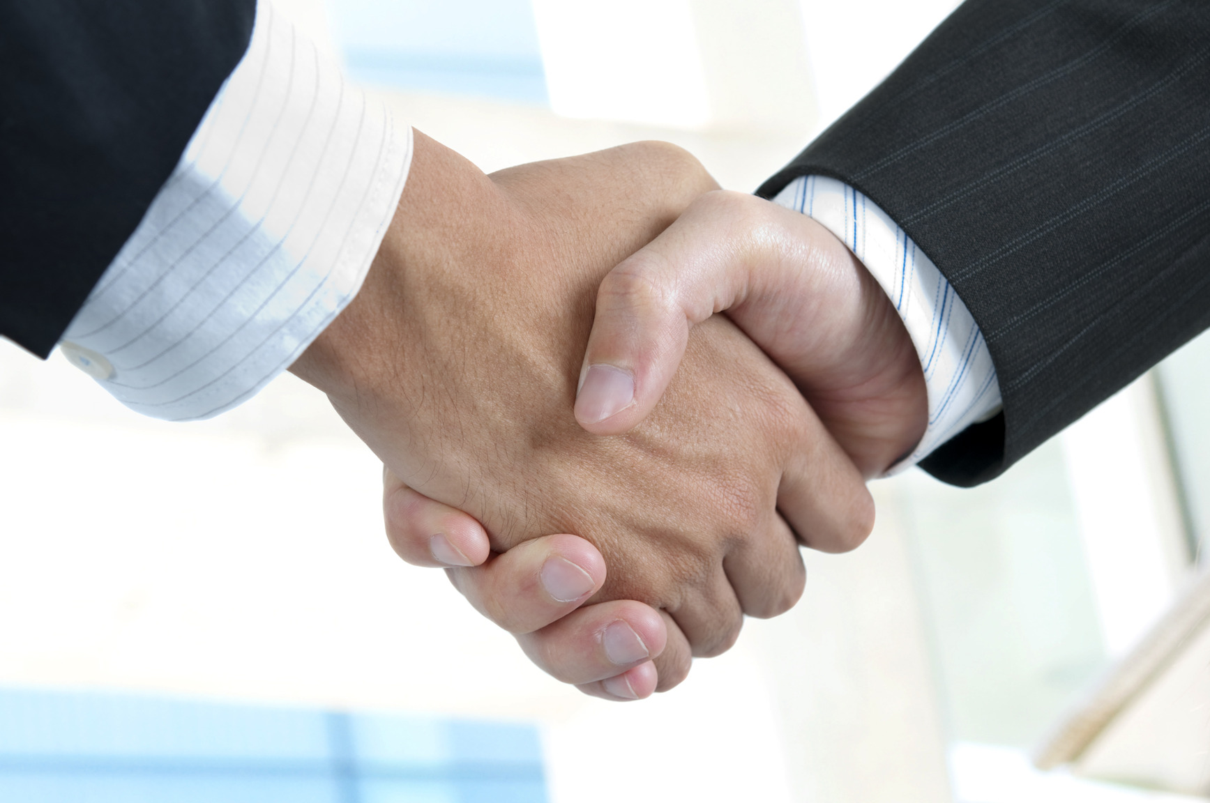 Asian businessman handshake with modern skyscrapers as background